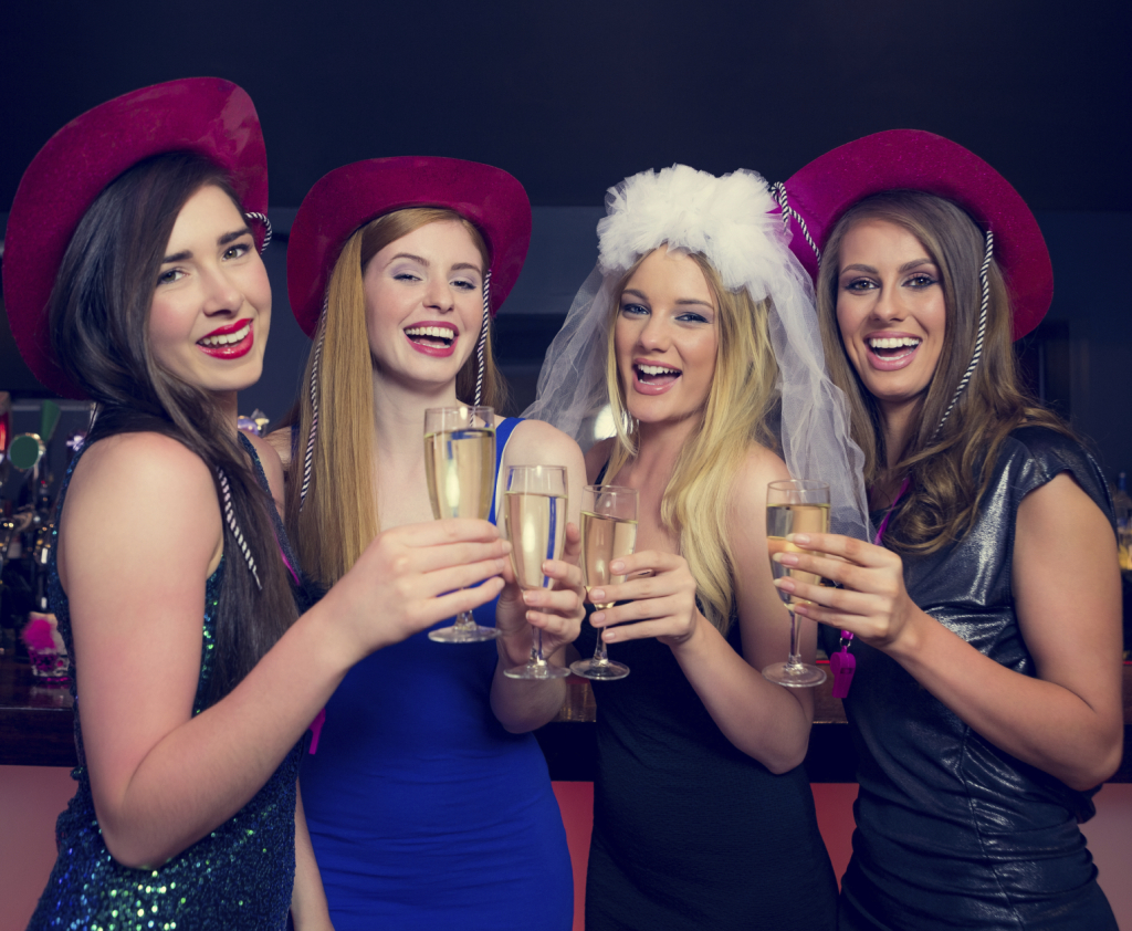 Laughing friends clinking champagne glasses at a hen night looking at camera