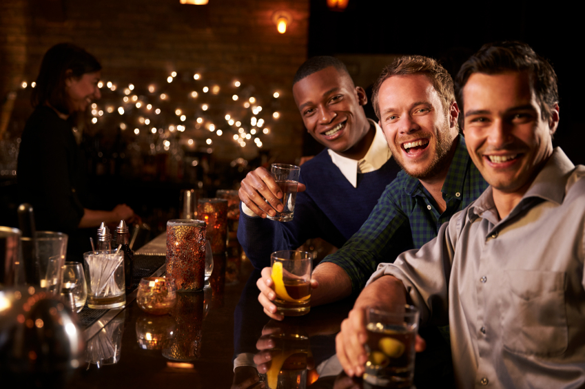 Portrait Of Male Friends Enjoying Night Out At Cocktail Bar